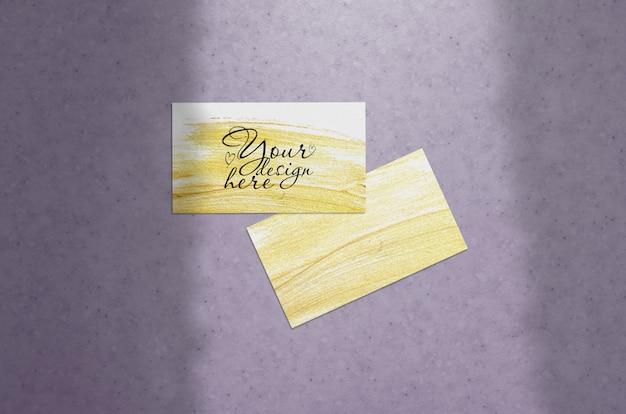 Maquete de cartão de visita em um fundo pupur com sombra de cortinas
