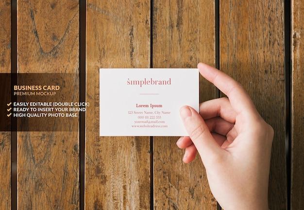 Maquete de cartão de visita segurado por uma mão em uma mesa de madeira
