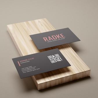 Maquete de cartão de visita simples e elegante em preto sobre pedestal de madeira