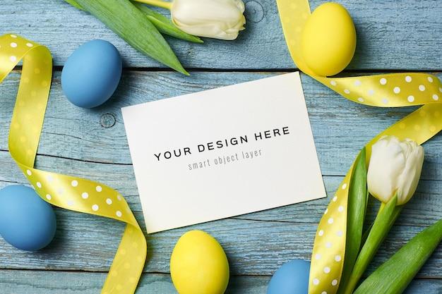 Maquete de cartão do feriado de páscoa com ovos coloridos, fitas e tulipas