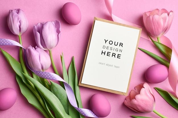 Maquete de cartão do feriado de páscoa com ovos coloridos, fitas e tulipas Psd Premium