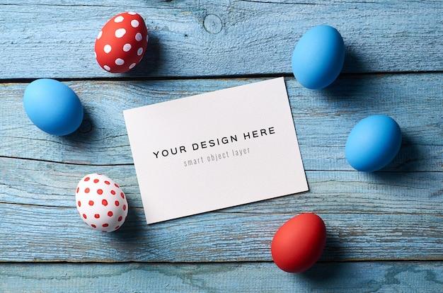 Maquete de cartão do feriado de páscoa com ovos coloridos na mesa de madeira.