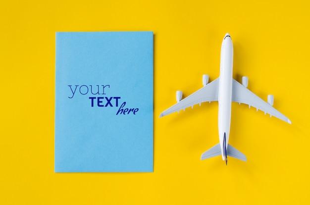 Maquete de cartão em branco com brinquedo avião. conceito de viagens de verão.