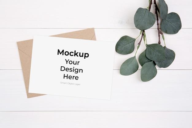 Maquete de cartão em branco e folha na mesa de madeira