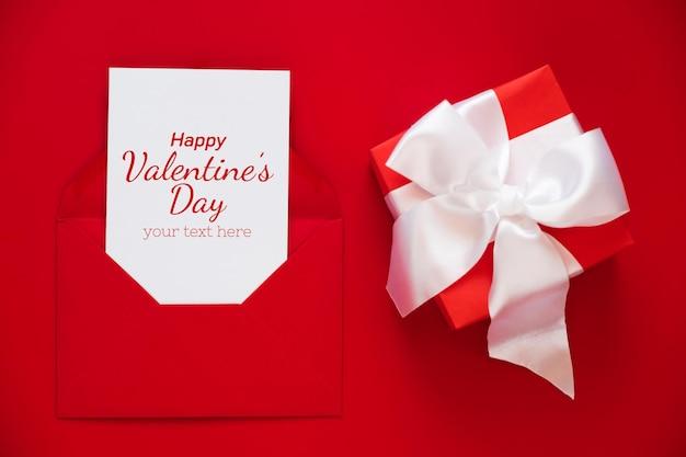 Maquete de cartão em envelope e presente sobre fundo vermelho.