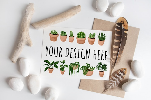 Maquete de cartão postal entre elementos rústicos, stcks, seixo branco e penas.