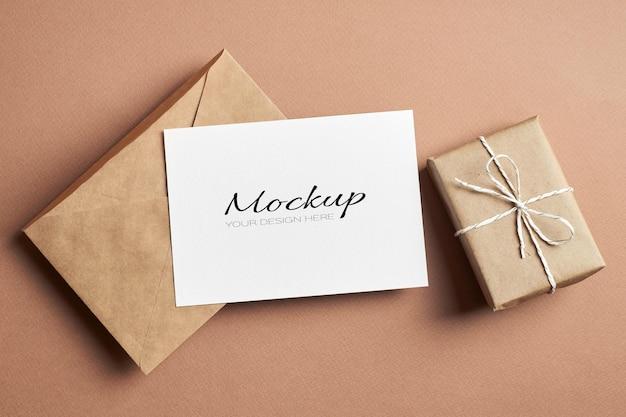 Maquete de cartão postal estacionário com envelope artesanal e caixa de presente