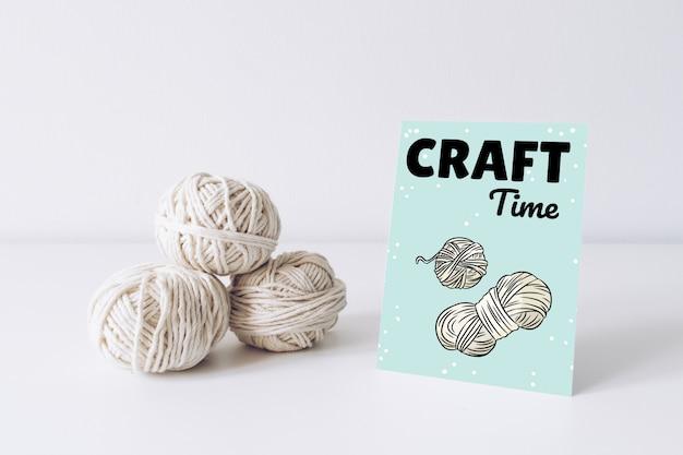 Maquete de cartão postal vertical com fio branco sobre uma mesa branca. linhas de imagem de boho de lã de corda.