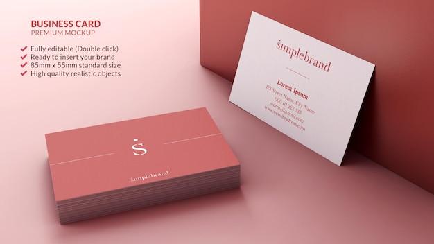 Maquete de cartões de visita em uma pilha e apoiada em um conceito de design de branding de parede