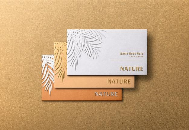 Maquete de cartões de visita modernos e luxuosos com efeito de relevo dourado
