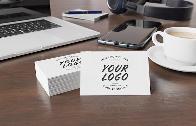 Maquete de cartões de visita na mesa de madeira com elementos de desktop renderização em 3d