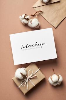 Maquete de convite ou cartão de felicitações com envelope, caixa de presente e flores naturais de algodão