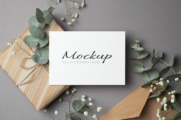 Maquete de convite ou cartão de felicitações com envelope, caixa de presente, flores de eucalipto e hypsophila