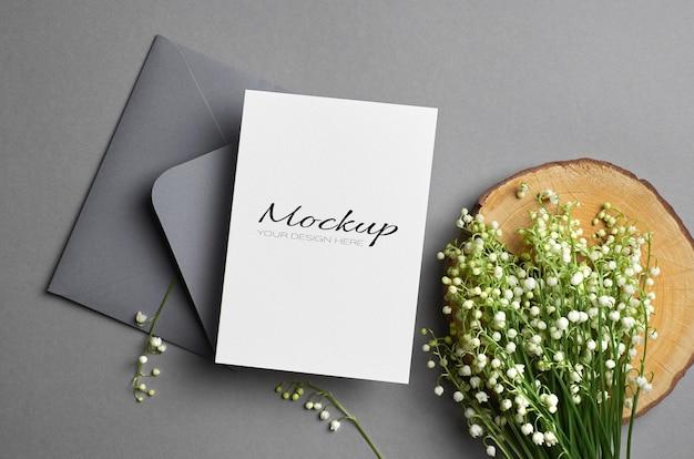 Maquete de convite ou cartão de felicitações com envelope e buquê de flores de lírio do vale