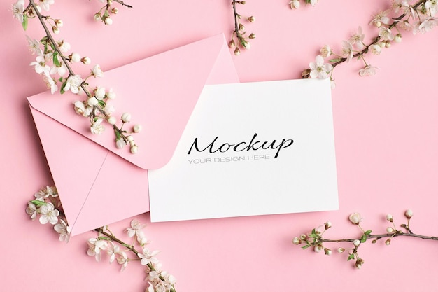 Maquete de convite ou cartão de felicitações com envelope e galhos de árvore de primavera com flores
