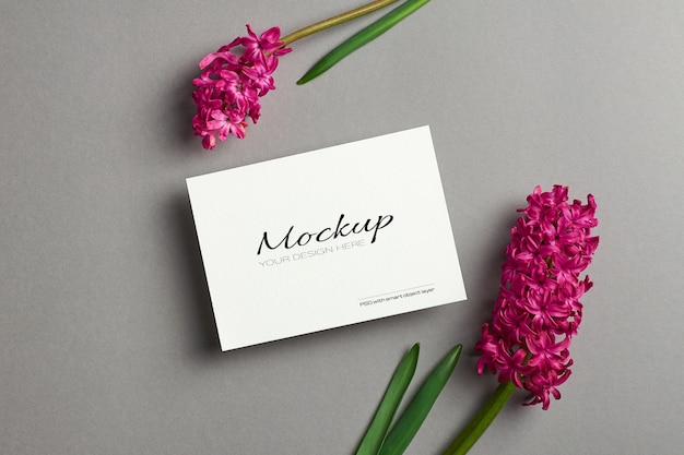 Maquete de convite ou cartão de felicitações com flores de jacinto da primavera em fundo de papel cinza