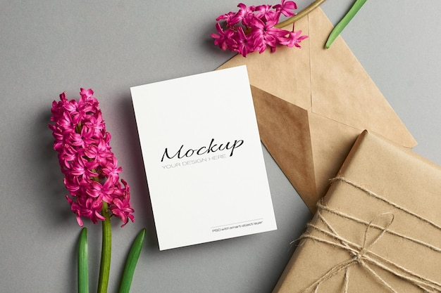 Maquete de convite ou cartão de felicitações com flores de jacinto e caixa de presente em fundo cinza