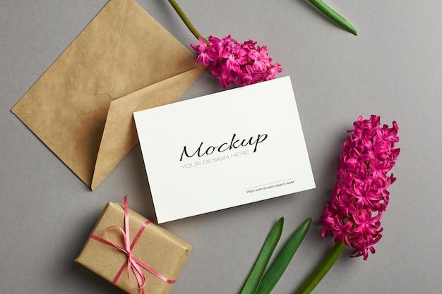 Maquete de convite ou cartão de felicitações com flores de jacinto, envelope e caixa de presente