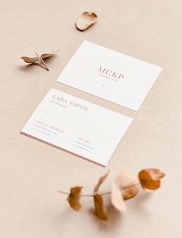 Maquete de dois cartões de visita brancos, frente e verso com folhas e cores naturais