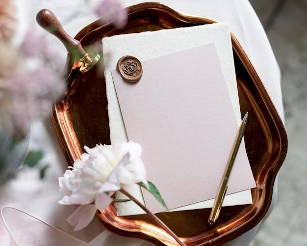 Maquete de envelope estampado em branco em uma bandeja metálica