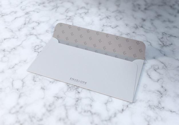 Maquete de envelope meio aberto com fundo de textura de mármore branco
