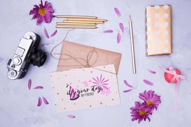 Maquete de feliz aniversário com envelopes amarrados e flores
