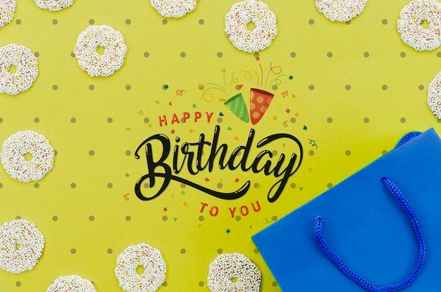 Maquete de feliz aniversário com sacola de compras e donuts