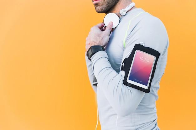 Maquete de fitness com homem com smartphone no braço