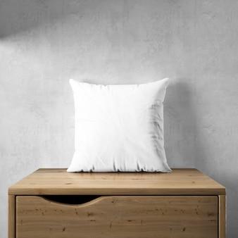 Maquete de fronha branca em um móvel de madeira