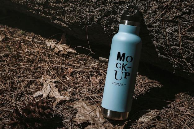 Maquete de garrafa de água na floresta