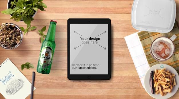 Maquete de garrafa de cerveja e tablet tablet fundo de madeira