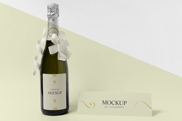 Maquete de garrafa de champanhe com fitas brancas e laços