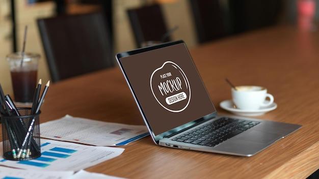 Maquete de laptop de espaço em branco com papéis financeiros, material de escritório na mesa de madeira do escritório