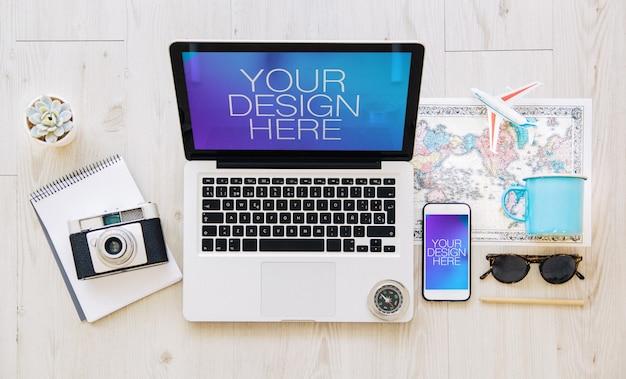 Maquete de laptop e celular com elementos de viagem