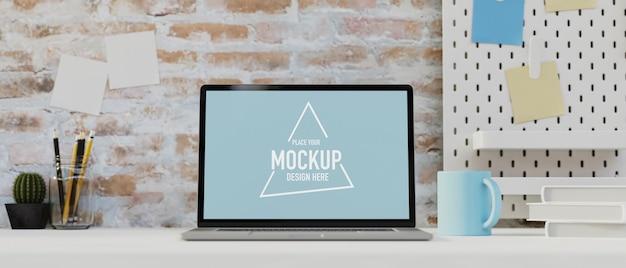 Maquete de laptop na mesa branca decorada com papelaria, planta, prateleira, coisas e parede de tijolos, design de conceito de sala de loft de escritório, renderização 3d, ilustração 3d