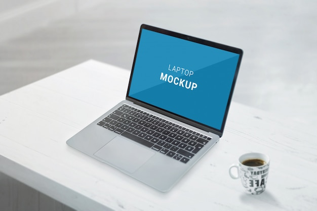 Maquete de laptop na mesa de escritório branco. xícara de café ao lado
