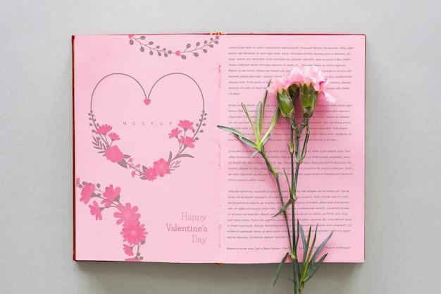 Maquete de livro aberto com flor para dia dos namorados