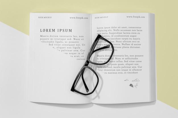 Maquete de livro aberto de vista superior com óculos