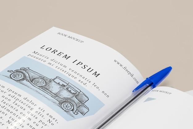 Maquete de livro aberto em close-up com caneta