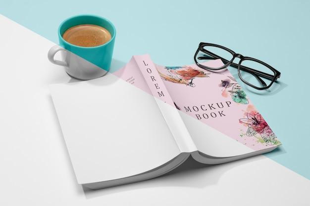 Maquete de livro aberto virado em ângulo alto com óculos e café