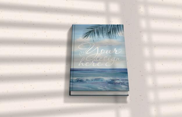 Maquete de livro com sombras na superfície da luz