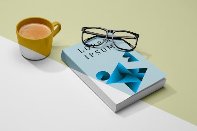 Maquete de livro de ângulo alto com óculos e café