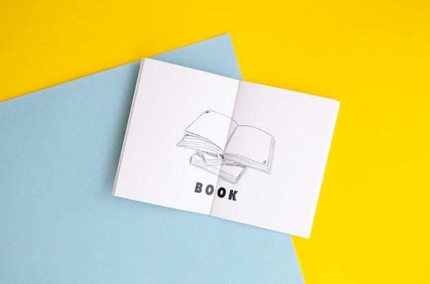Maquete de livro de desenho sobre fundo bicolor