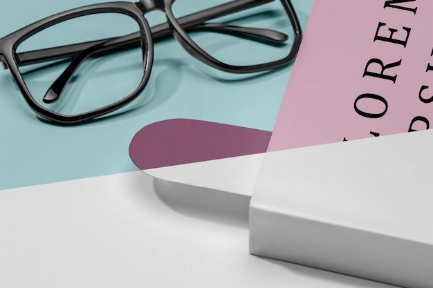 Maquete de livro em close com óculos e marcador