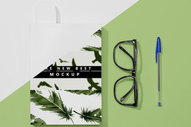 Maquete de livro plana com óculos e caneta