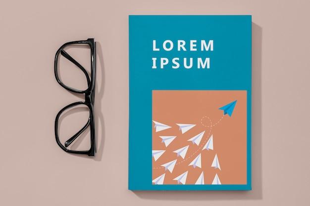 Maquete de livro plana com óculos
