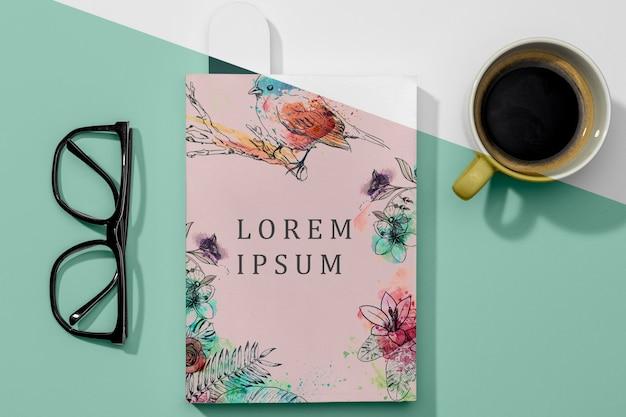Maquete de livro plano com óculos e café
