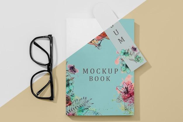 Maquete de livro plano com óculos e marcador