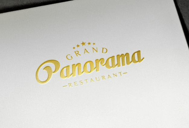 Maquete de logotipo de folha de ouro em relevo em papel branco