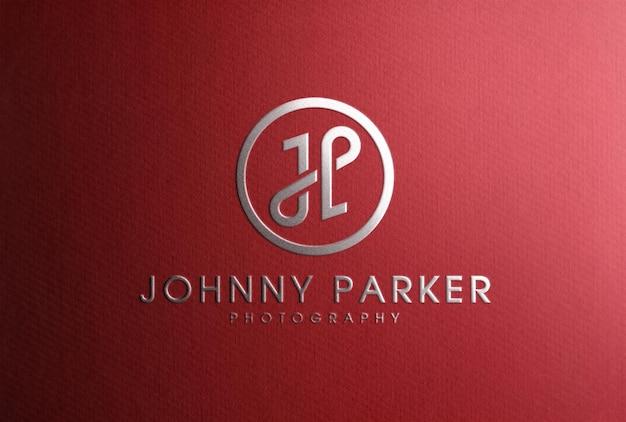 Maquete de logotipo de luxo de folha de prata estampada em papel vermelho